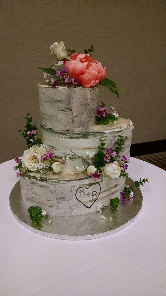 Three tier oval, rustic cake with birch design and silk flowers.  This cake serves serves approximately 113 guests.  $3.50/Serving $395.50