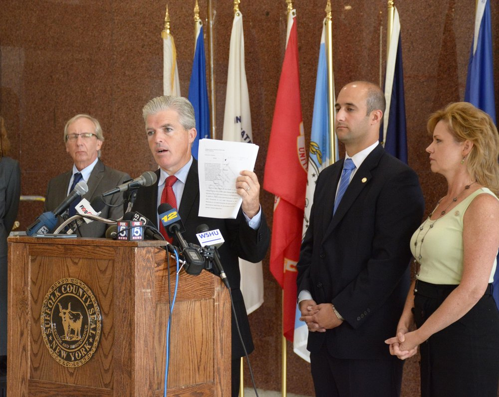 Suffolk County Executive Steve Bellone holds a copy of the lawsuit during a press conference on Wednesday. Standing behind him are Dennis Brown, county attorney; Legislator Robert Calarco; and Legislator Sarah Anker. RONNY REYES / WSHU