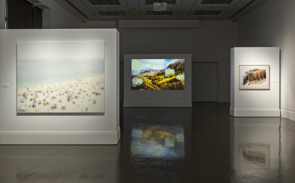 The View From Here , Main Gallery, Art Gallery of Mississauga. Left: A Young Lover's Dream , 2013. Center: Clive Holden, Internet Mountains Video 1 , 2014. Right: Jason Gowans, Landscape 3 , 2013. Photo by Toni Hafkenscheid.