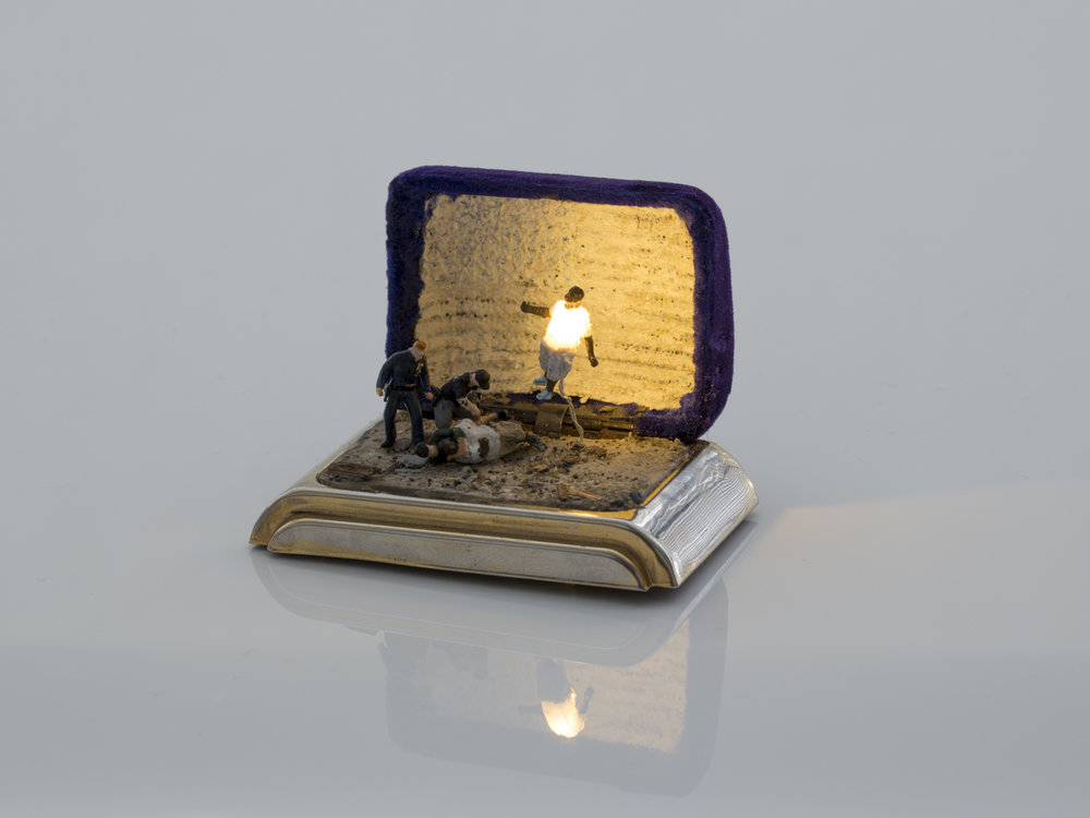TALWST, Por qué? , reclaimed 1950's ring box, model putty, plastic, crushed rock, gold leaf, Acrylic paint, 3v led light. 3v coin battery. Flag: encaustic and ball point on gauze, 2014. Photo by Todd Duym.