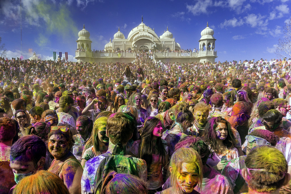 Festival participants enjoy Holi celebrations, replete with colourful powder