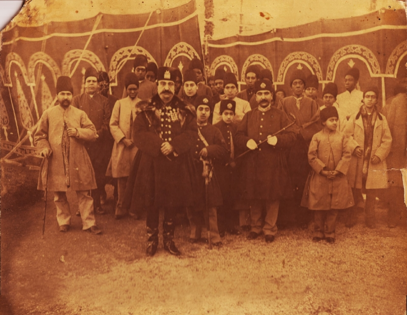 This 1895 photo was taken by one of the most important photographers of the Qajar era, Abdullah Qajar (1850-1909). In this rare photo, Nasser al-Din Shah is accompanied by his sons, members of court, and most of his favourite and influential slaves. There are 10 African eunuchs in the photo, among them Haji Firouz (the one wearing white and standing behind the king) who was one of the most trusted slaves of the king. Outside one of the royal tents, Norouz 1895 (Iranian New Year), possibly Shahrestanak, Tehran. | Caption and photograph attributed to Dr. Pedram Khosronejad in  The Guardian