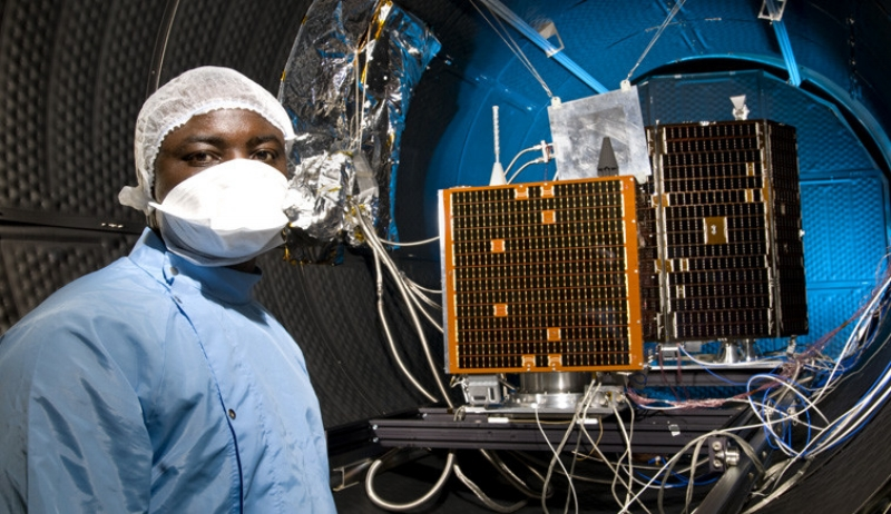 Bosun Yusuf, Thermal Subsystem Enginer, Surrey Satellite Technology Limited, (SSTL), and Know How Technology Transfer, KHTT, infront of SSTL designed spacecraft 'Nigeria Sat-2' & 'NX