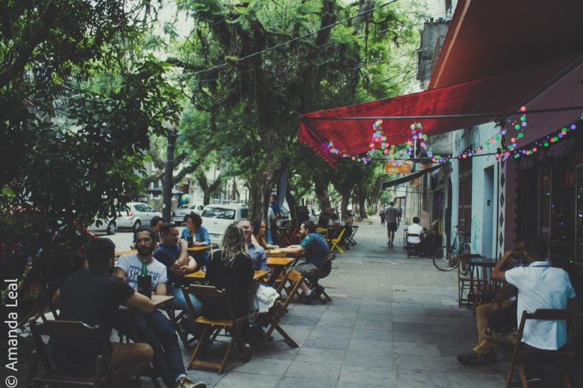 As mesas na calçada, junto às arvores da Rua da República, em frente ao Porto Carioca: ambiente agradável num final de tarde no verão