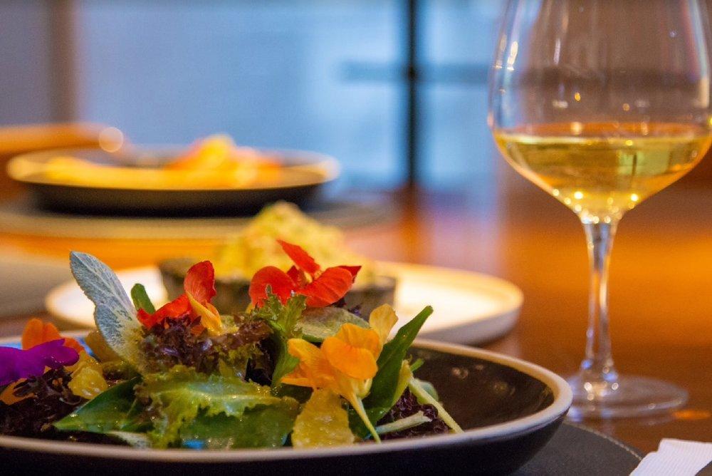 Salada de PANCs, feita com ingredientes orgânicos, locais e sazonais, acompanhada de vinho branco da Grand Cru: opção do cardápio do novo restaurante da Padre Chagas (Foto/José Antônio Kalil)