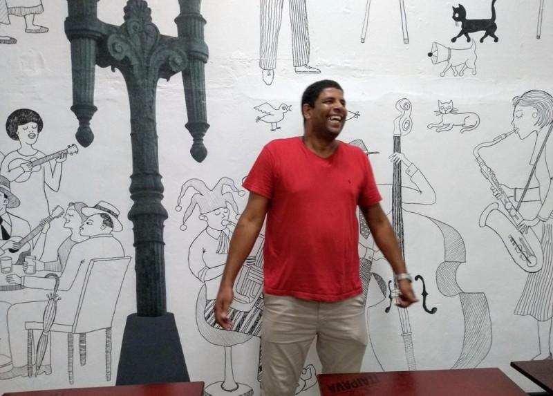 Gelson, dono do boteco, em frente à parede redecorada por artistas do coletivo Casa Musgo