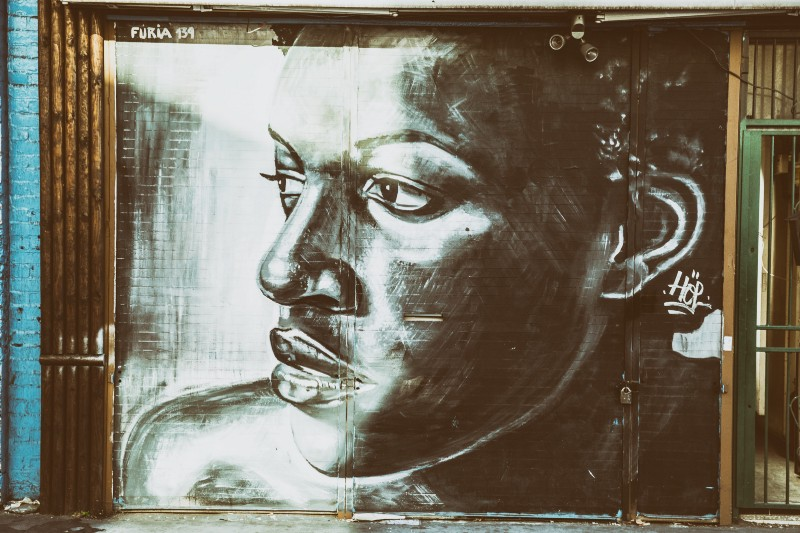 Gender and Sexuality - Tom Eversley for Iso Republic. [IMAGE DESCRIPTION: a Black woman is painted outside at 3/4 profile over her right shoulder. The grate of a door is visible on the right side of the frame].