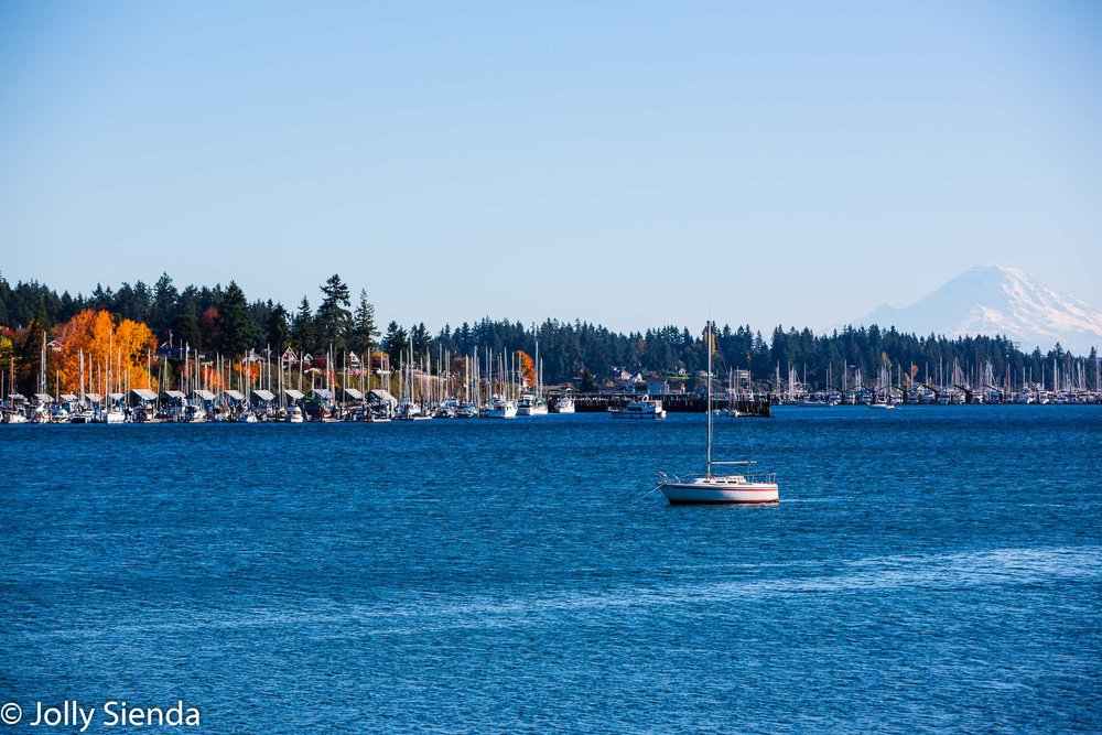 Mount Rainier looks over Liberty bay and a sailboat