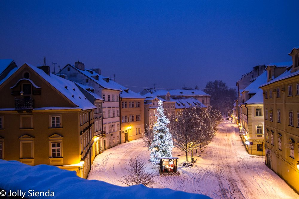 Snow covered row houses at dawn surround a park with a Nativity