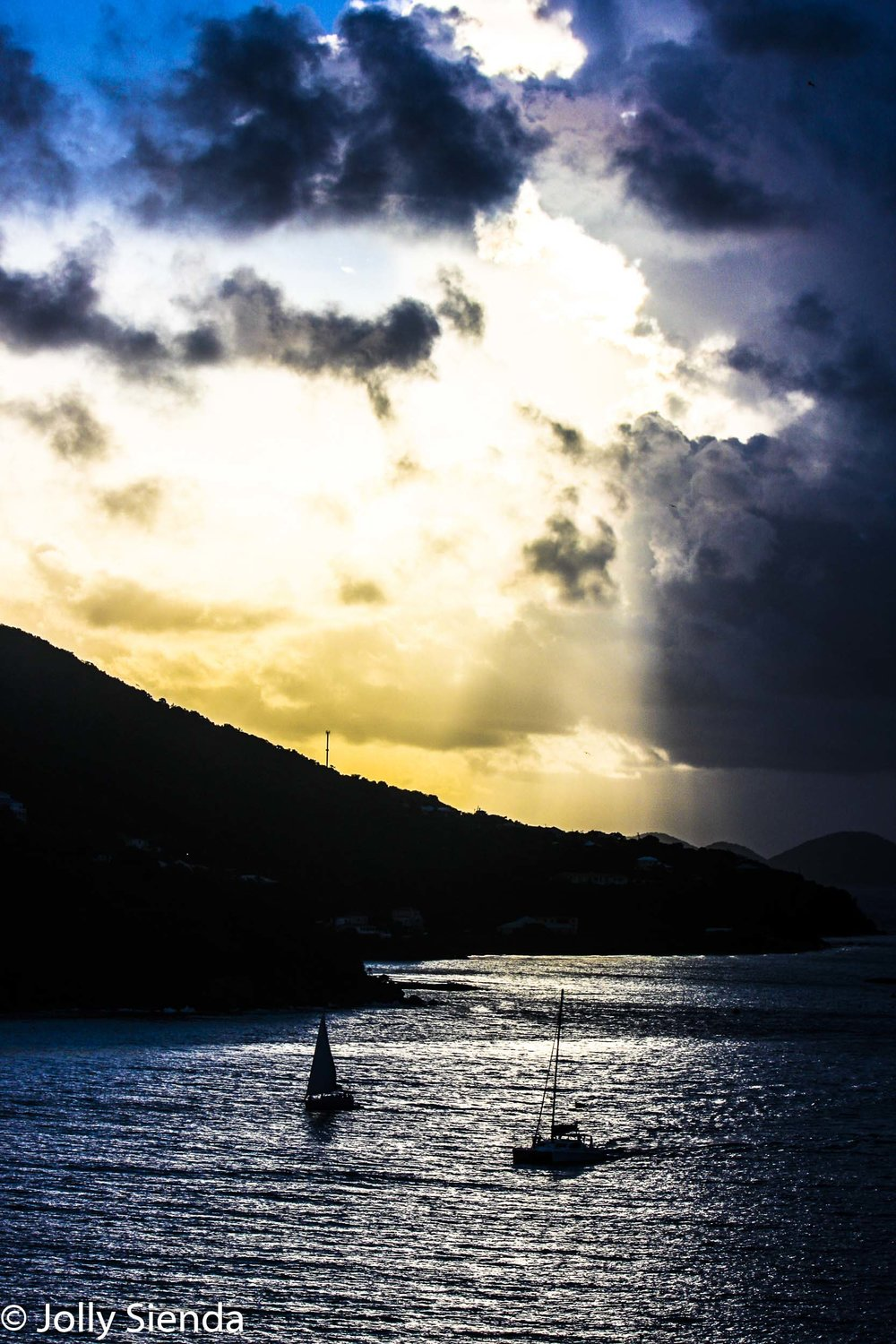 The sun breaks through clouds sending light onto the water, boat