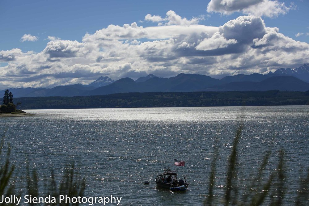 Boat with an American Flag on Hood Canal sailing towards the Olympic Mountains.