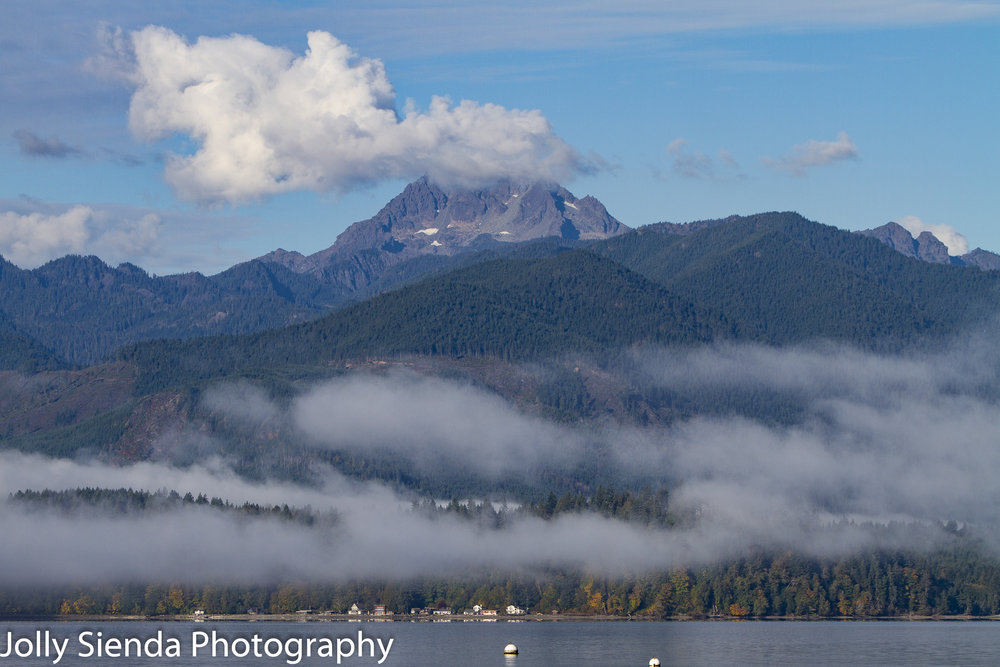 The Brothers Mountain, Olympic Mountains, peaks over light pillows of fog on the Hood Canal.