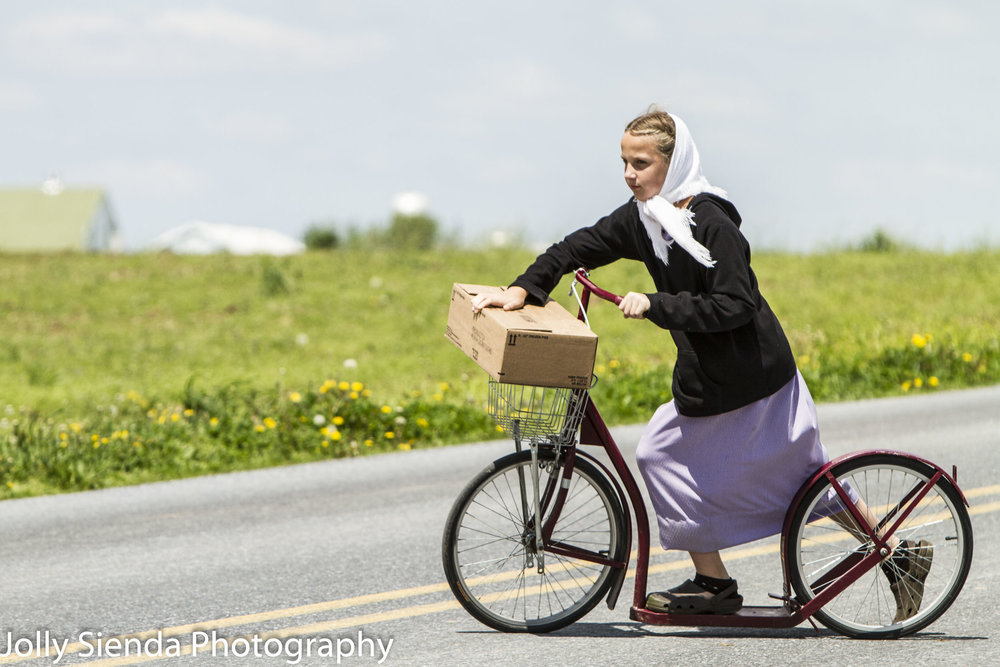 Amish girl balances a package on her basket  of her scooter bike