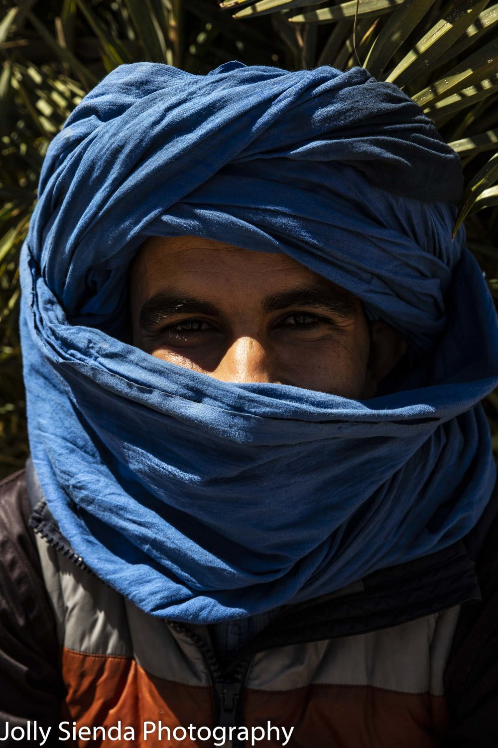 Man wears a blue turban and smiling eyes