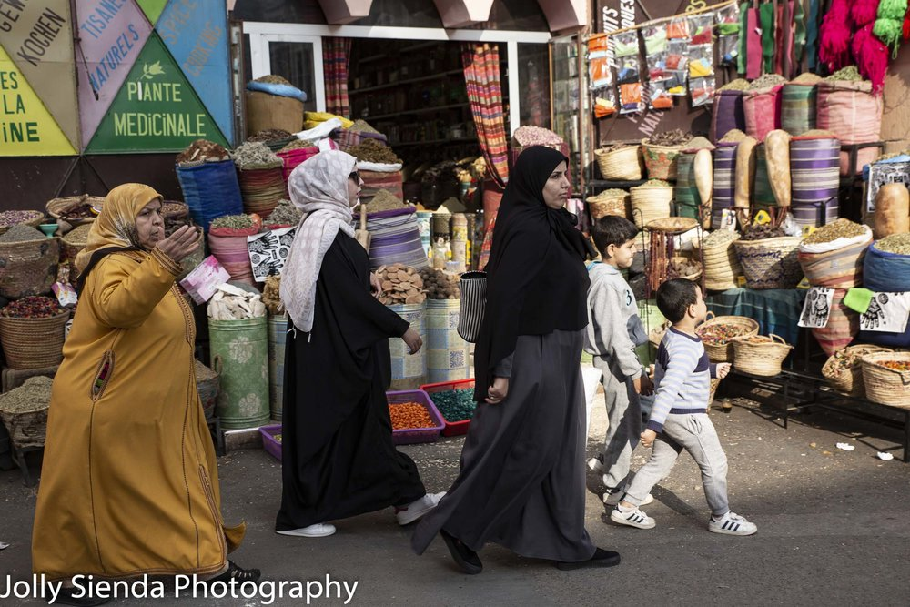 Moroccan people pass shopping stalls