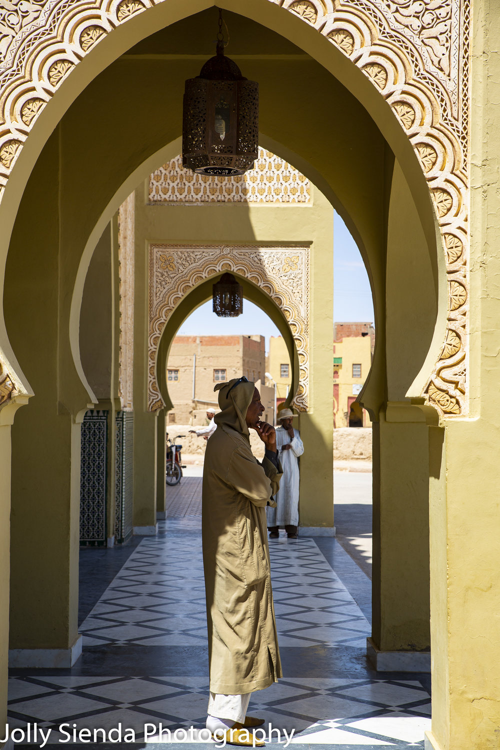 Man in a  djellaba stands in an Islamic archway