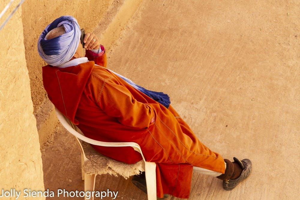 Man in a Jabala rests in a chair