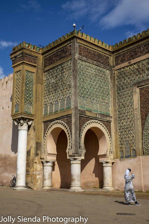 Muslim woman takes a picture of Bab al-Mansour mosaic tile