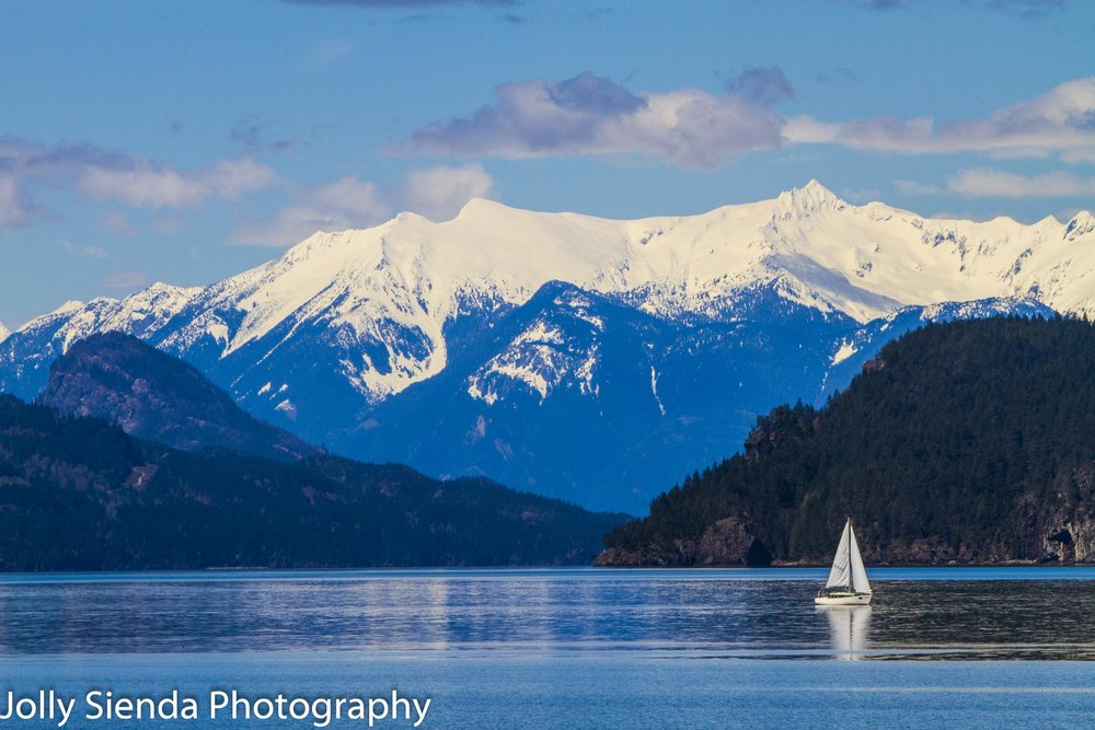 Sailboat on Harrison Lake and snow capped mountains