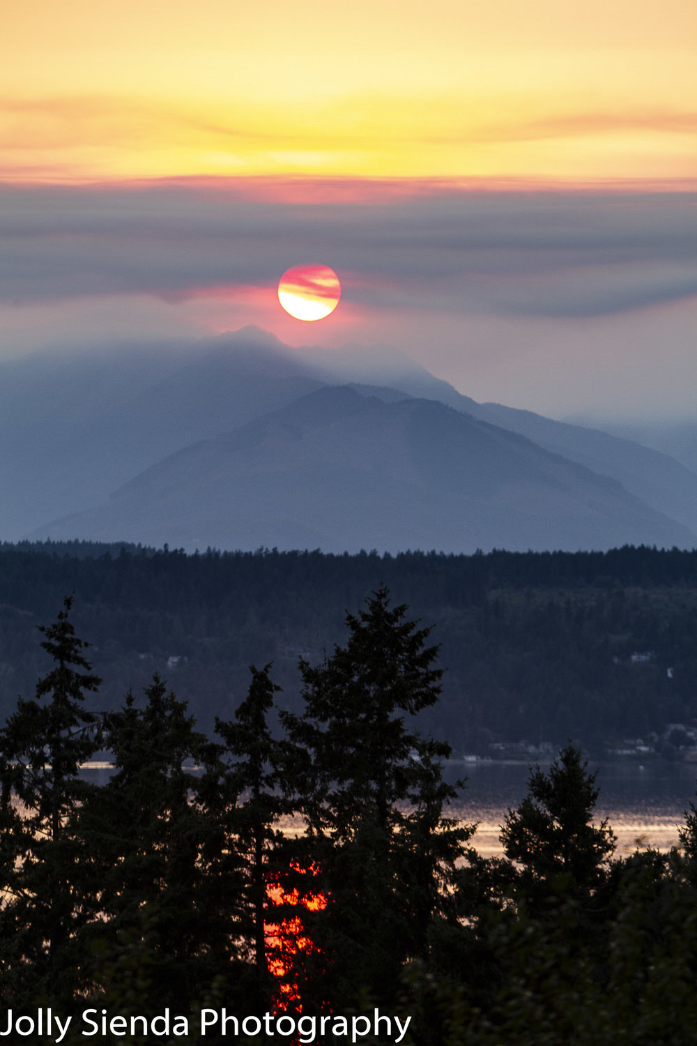 Smoke drifts past the sun and over the mountains