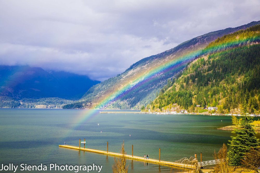 Rainbow arches over the dock and Harrison Lake