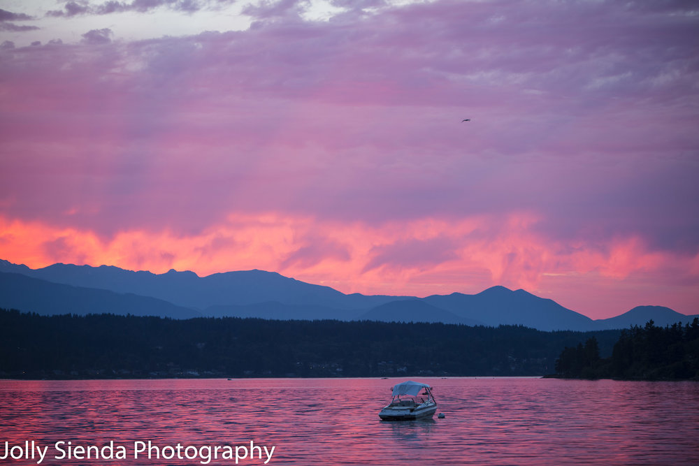 Magenta sunset rains color over a boat on the bay and the Olympi