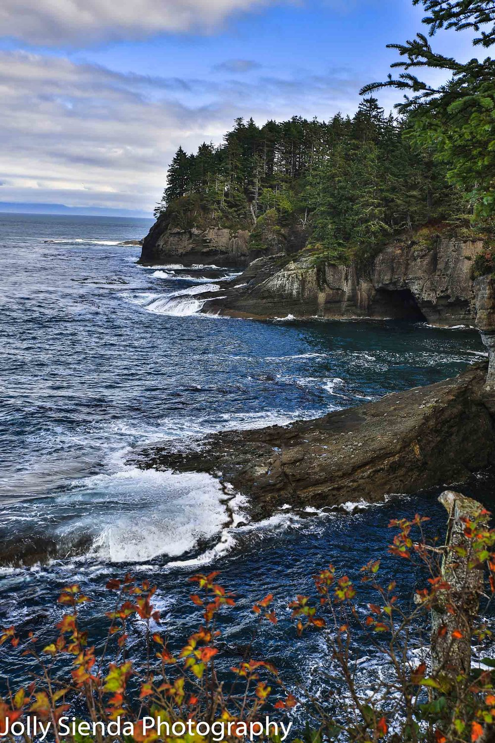 Caves and bluffs at Cape Flattery with water crashing onto the b