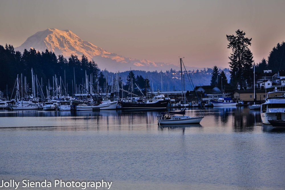 Sunset on Mount Rainier as a sailboat glides by in a marina