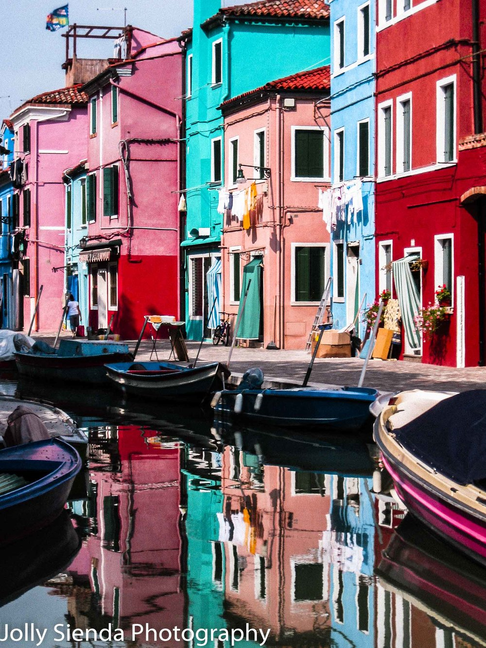Burano's Colored Houses, on a canal, with colored boats and a re