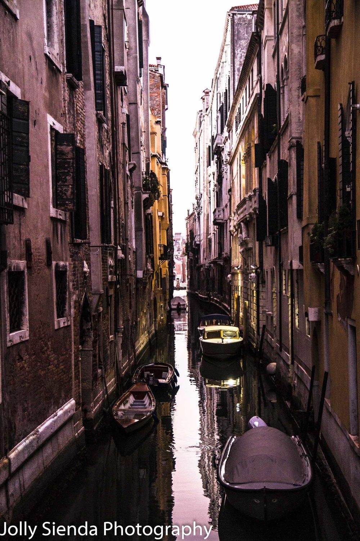 Narrow Venetian canal and boats at sunrise