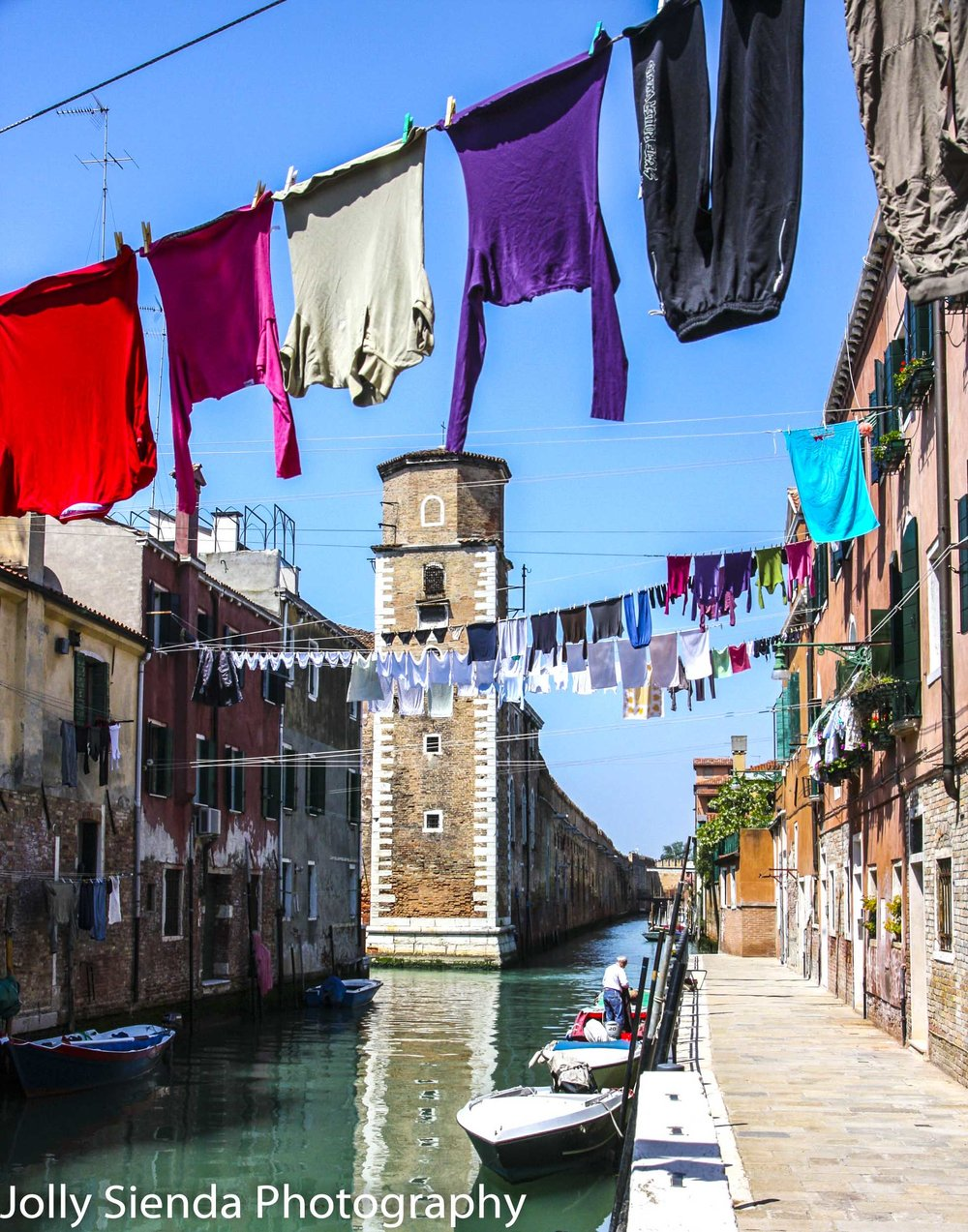 Quite Venetian canal with hanging laundry, boats, and a man in a