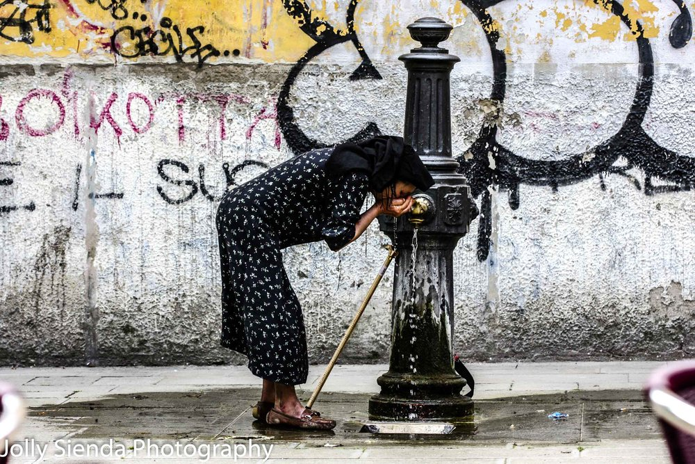 Venetian Gypsy Woman Drinks Water from her Hands over a  Fountai