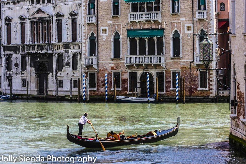 Gondolier steers his shiny, black gondola through a canal near V