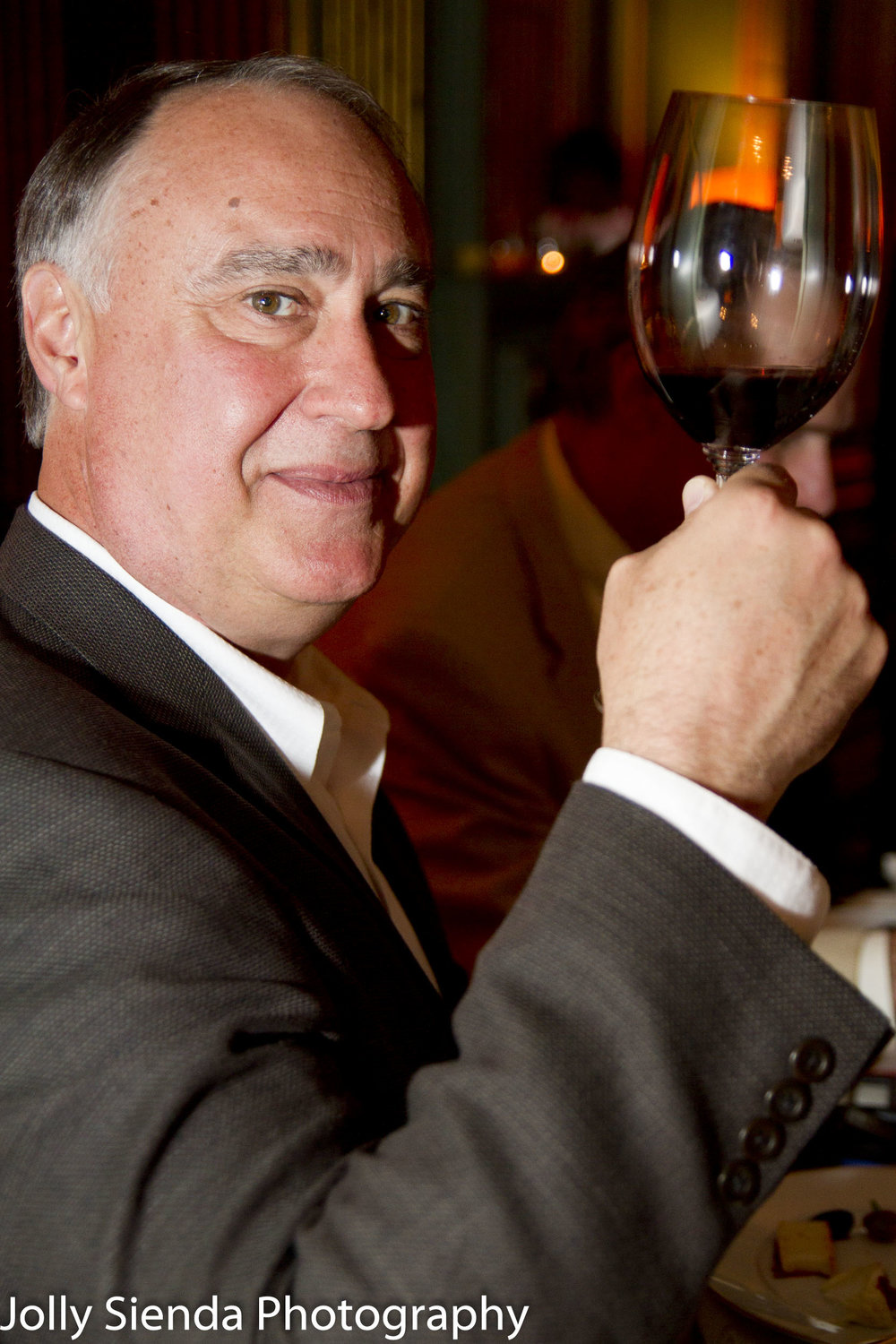 Portrait of a man making a toast with a glass of wine