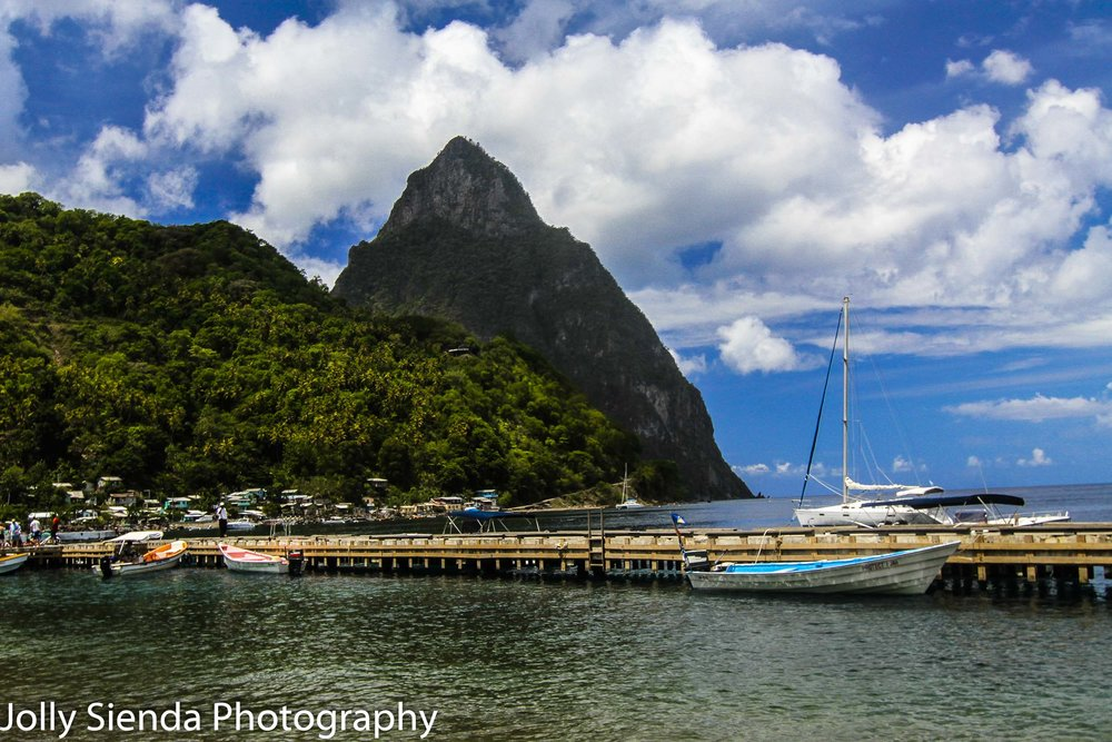 The long dock with colored boats with the Pitons and a village i