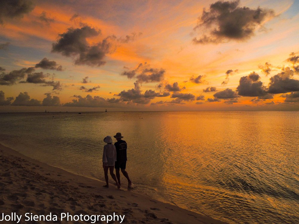 A couple walking on Seven Mile Beach during a golden, pink, suns