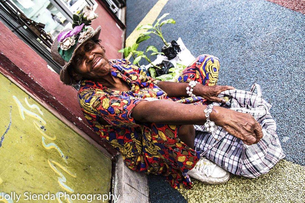 Old woman sells plants on the sidewalk