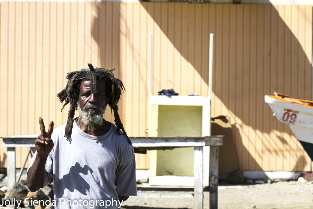 Portrait of a Rastafarian man making a peace sign with his hand