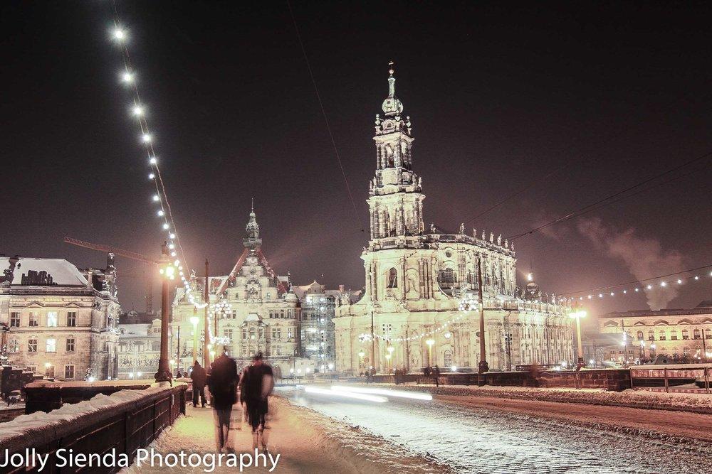 People walking across a snow packed Augustus Bridge, at night, w