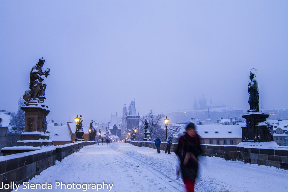 Woman in red crosses the Saint Charles Bridge while its snowing
