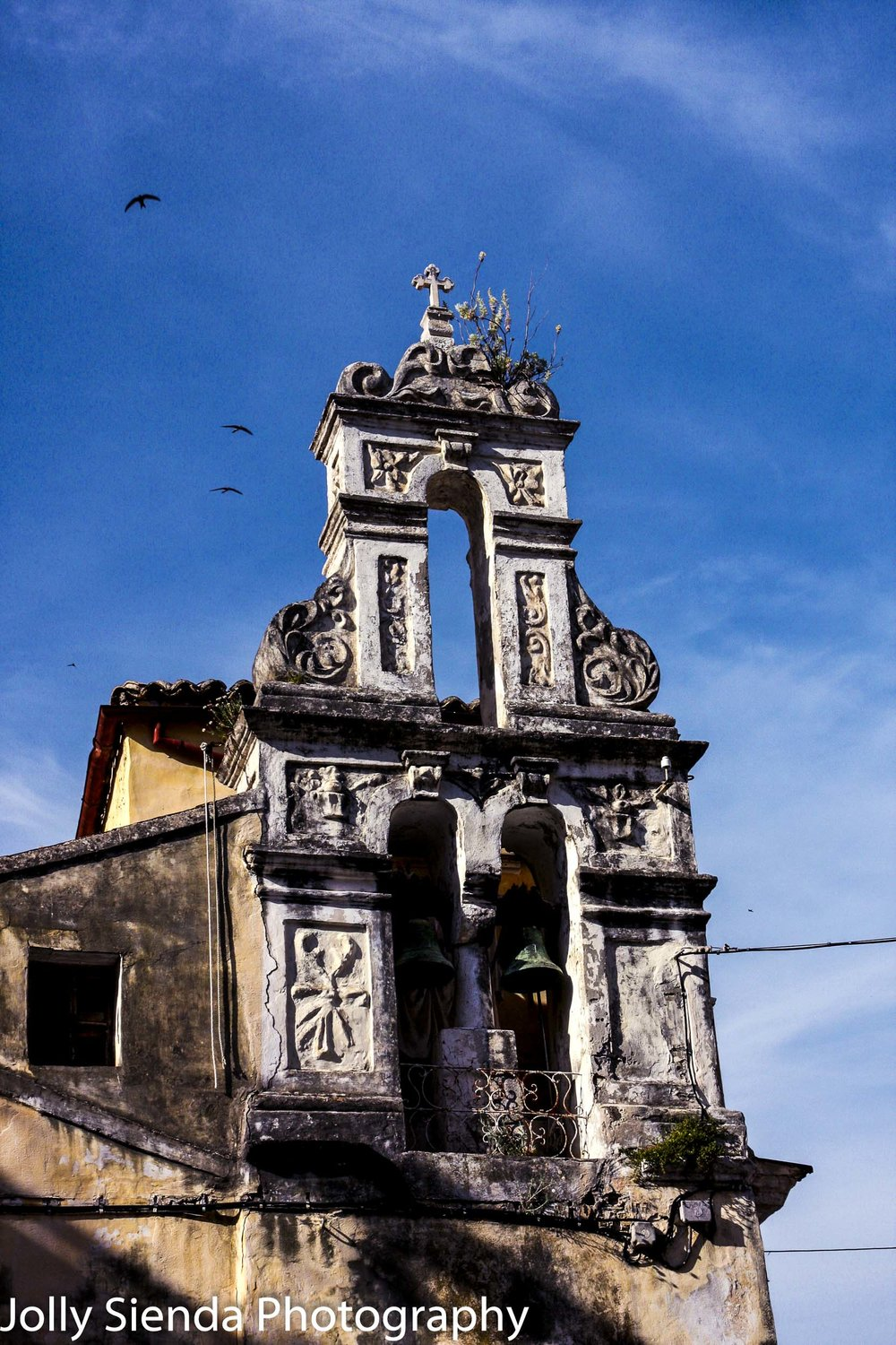Old, ornate church facade with bronze bells and seagulls