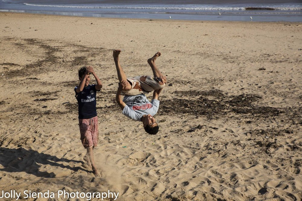 Men doing somersaults on the beach