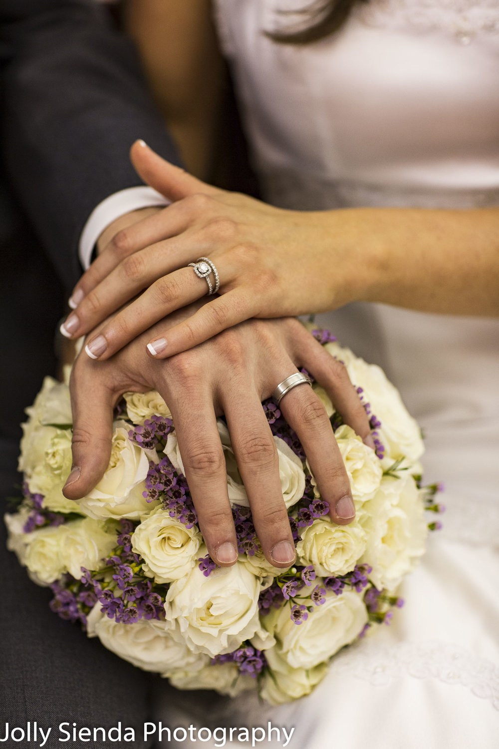 Hands clasped with his and her diamond wedding rings over weddin