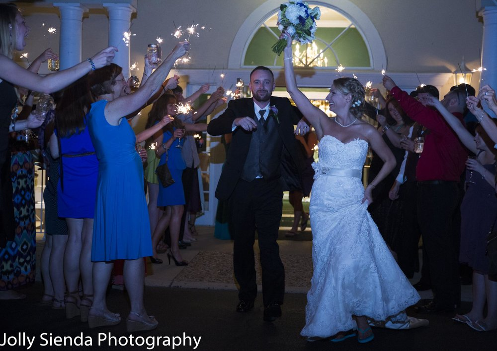 Capturing the wedding reception action as the bride and groom leave while guests cheer them on with lit sparklers.