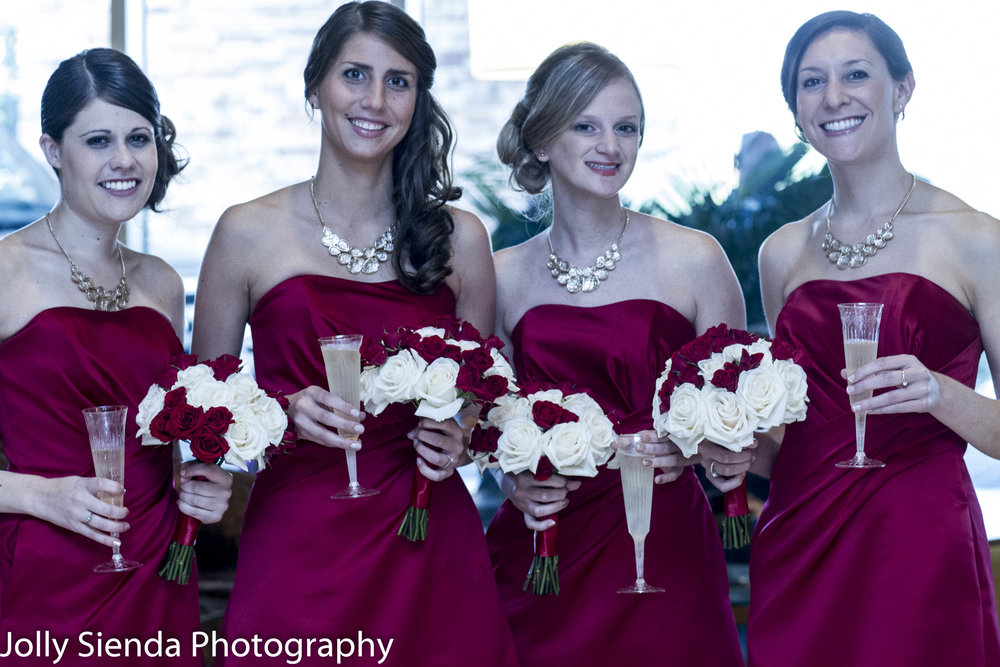 Bridesmaids gather for a photo in their Valentines red dresses and red and white roses