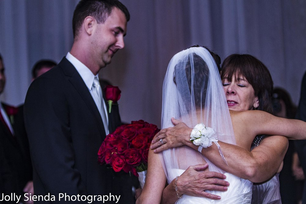 Bride at the alter gets a hug from her mother with the groom looking on and smiling
