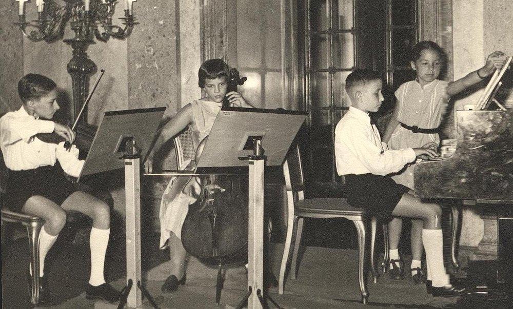 """鲁迪·布赫宾德(钢琴)、彼得鲁迪·古特(Peter Guth)(小提琴)和海迪·李绍尔(Heidi Litschauer)(大提琴)组成的传奇性""""维也纳少年三重奏乐队,他1961年首次在维也纳洛布科维茨宫中公演。"""