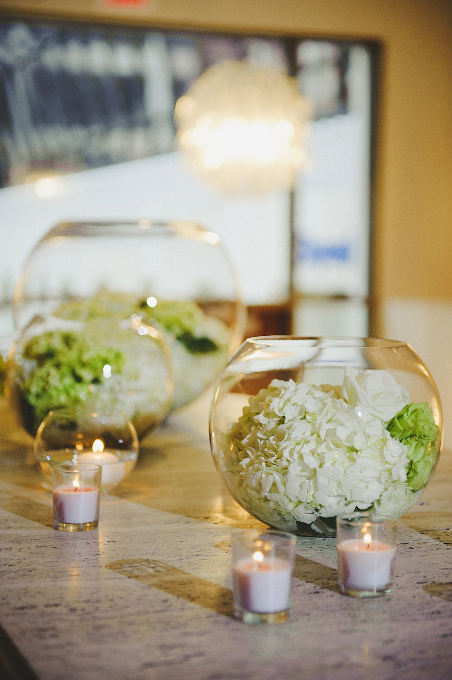 White floral filled glass globes for white and green wedding by Yellow Canary Floral & Event Design