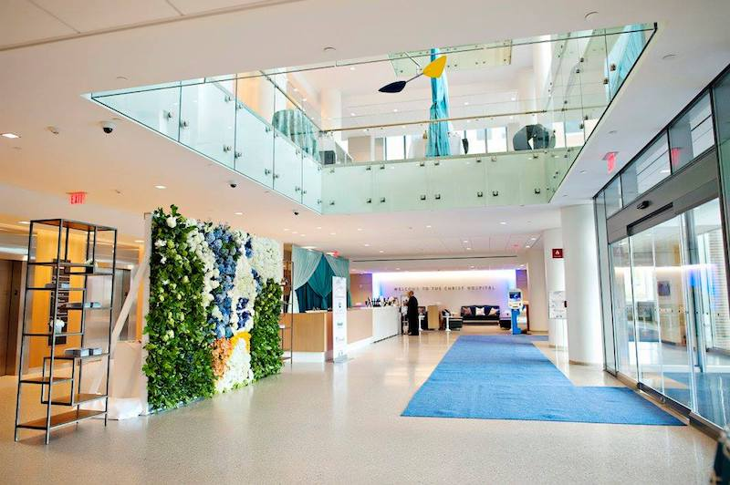 A blue, white, green and yellow floral wall was the perfect welcome for The Christ Hospital's Joint and Spine Center's Grand Opening entrance.