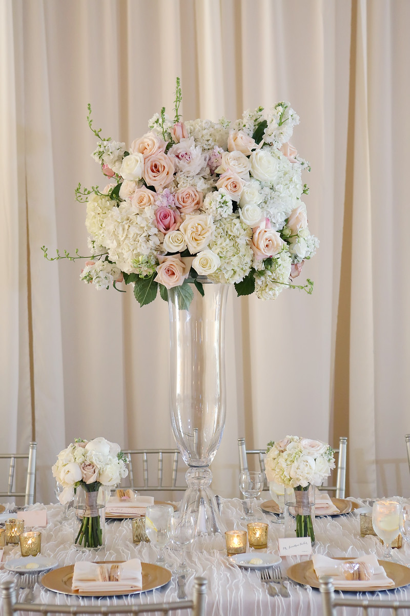 Pink, white, and gold wedding reception in Cincinnati at The Center with florals by Yellow Canary Floral and Event Design. Gold chargers, gold votives, and silver chiavari chairs transformed the reception space.